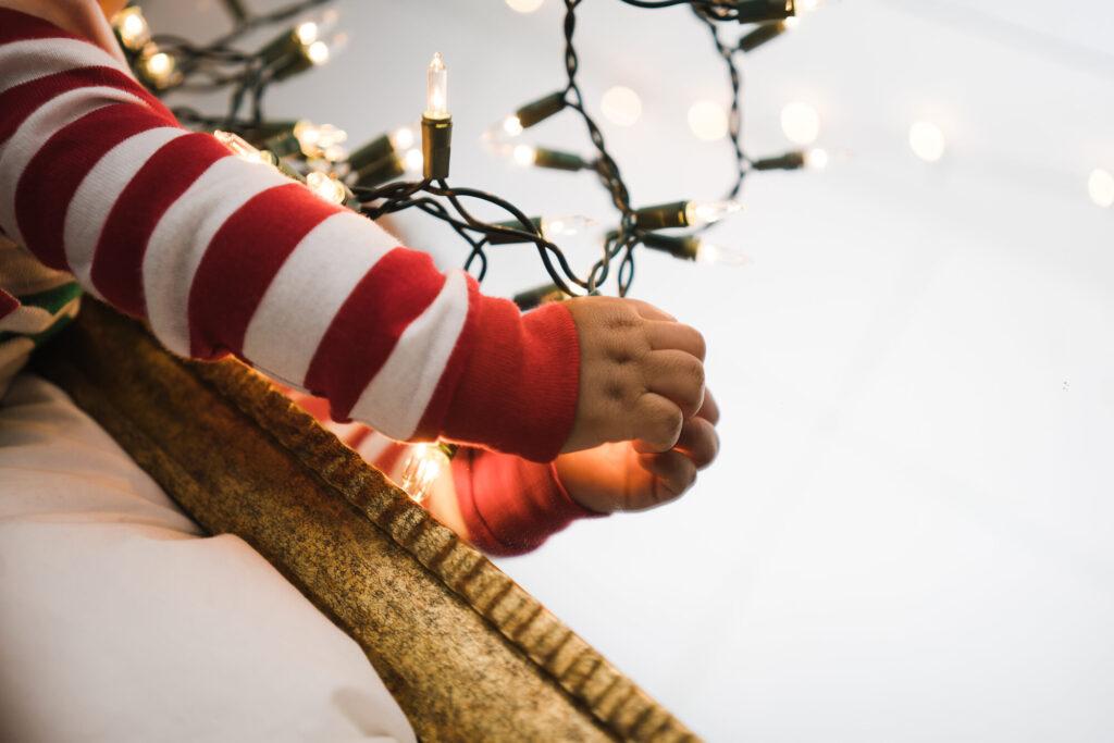 kid holding christmas lights